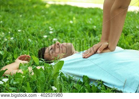 Young Woman Performing Cpr On Unconscious Man Outdoors, Closeup. First Aid