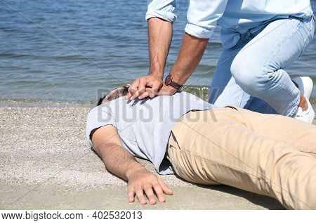 Passerby Performing Cpr On Unconscious Young Man Near Sea. First Aid