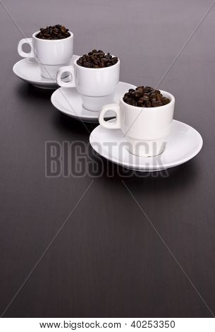 3 White Cups With Coffee Beans On Brown Table