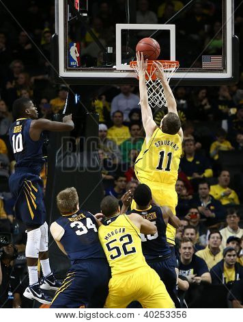 BROOKLYN-DEC 15: Michigan Wolverines guard Nik Stauskas (11) dunks the ball past West Virginia Mountaineers guard Eron Harris (10) at Barclays Center on December 15, 2012 in Brooklyn.