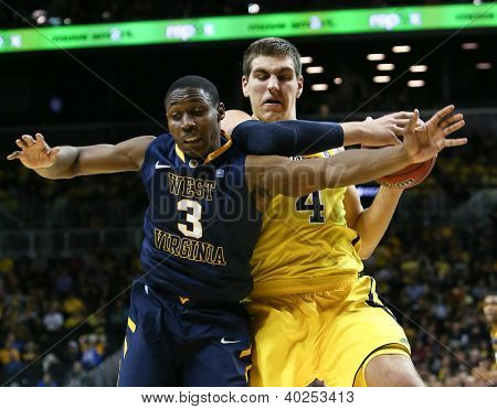 BROOKLYN-DEC 15: West Virginia Mountaineers guard Juwan Staten (3) and Michigan Wolverines forward Mitch McGary (4) battle for the ball at Barclays Center on December 15, 2012 in Brooklyn.