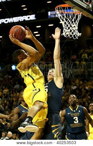 BROOKLYN-DEC 15: Michigan Wolverines guard Trey Burke (3) goes up for a shot as West Virginia Mountaineers forward Volodymyr Gerun (35) defends at Barclays Center on December 15, 2012 in Brooklyn.