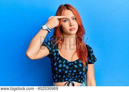 Young beautiful redhead woman wearing casual clothes over blue background pointing unhappy to pimple on forehead, ugly infection of blackhead. acne and skin problem