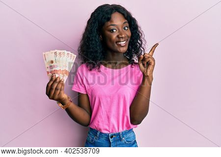 Beautiful african young woman holding 10 colombian pesos banknotes smiling happy pointing with hand and finger to the side