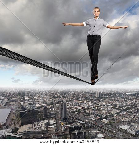 Business woman balancing high over a cityscape