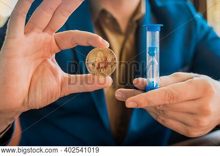Businessman Hands Hold Gold Cryptocurrency Bitcoin And Hourglass. Cryptocurrency And Bitcoin Concept