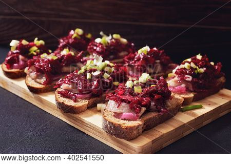 Traditional Russian Sandwiches With Spicy Beetroot Salad, Pickled Onions And Smoked Herring. Brusche
