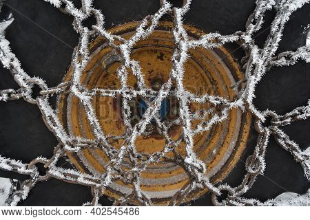 The Chain On A 4-wheel Drive Tractor Tire Is Coated With Hoar Frost.