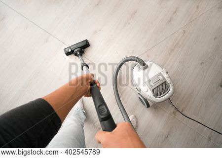 Man Using A Vacuum Cleaner At Home. Man Cleaning House. House Keeping Concept. First-person View