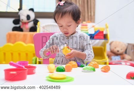 Cute Little Asian Toddler Baby Girl Child Having Fun Playing Alone With Cooking Toys, Slice And Play