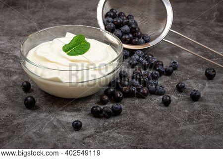 Fresh Blueberries In A Kitchen Strainer Together With Fresh Creamy Yogurt On Gray Background. Tasty