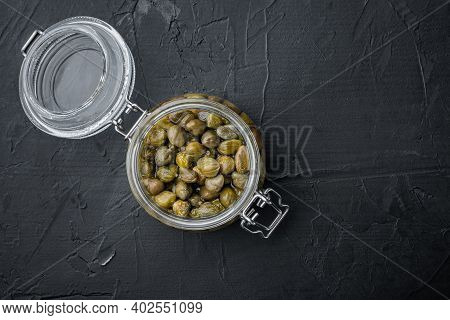 Baby Capers In Glas Jar, On Black Background, Top View  With Copy Space For Text