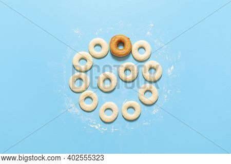 Preparing Doughnuts At Home, Raw Dough In A Ring Shape And One Fried Donut, On Blue Background. Top