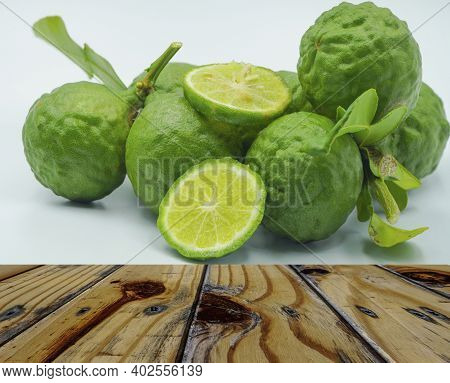 Wooden Table On Kaffir Lime Background. Mock Up For Your Product Display Or Montage.