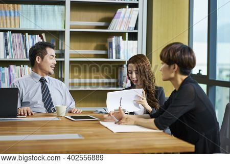 Three Asian Businesspeople Man And Woman Sitting At Desk Discussing Business Proposal In Office