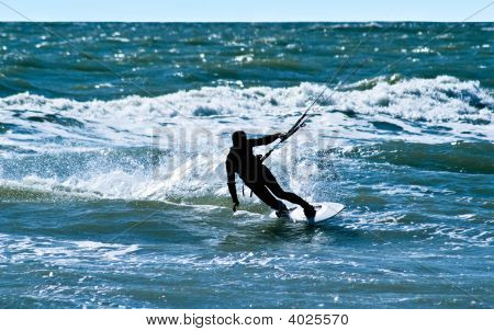 Silhouette Of A Kitesurfer On Waves Of A Sea