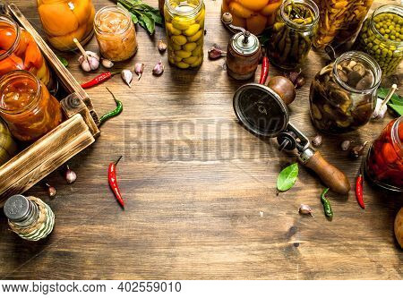 Marinated Vegetables And Mushrooms In Glass Jars With Seamer. On A Wooden Table.