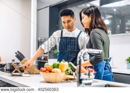Young Asian Family Couple Having Fun Cooking Together With Fresh Vegetable Salad On Table.happy Coup