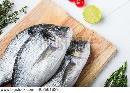 Raw Dorada Or Sea Bream Fish Set On Chopping Board With Herbs For Grill Uncooked  On White Textured