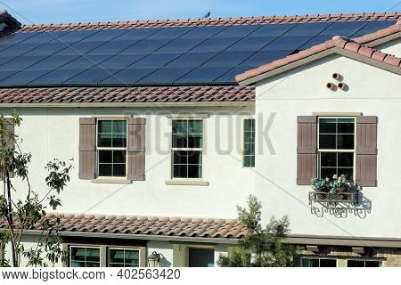 Solar Panels Creating Green Alternative Energy On A Tiled Rooftop Of A Residential Building Taken In