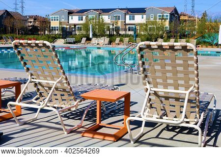 Modern Poolside Chairs Besides Small Outdoor Patio Tables Surrounding A Pool Taken In A Residential