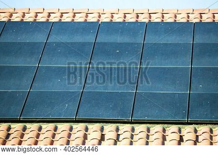 Energy Efficient Solar Panels On A Tiled Rooftop Creating Green Alternative Energy Taken In A Reside