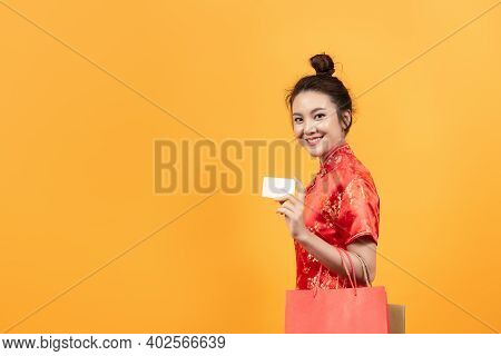 Beautiful Asia Girl Wear Cheongsam Hold Shopping Bags And Credit Card  In Chinese New Year On Yellow
