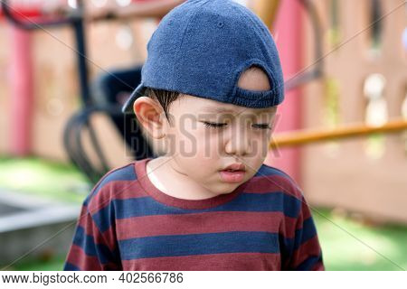 Asian Little Boy Portrait Tired Expression In The Park On The Playground For Kids & Children