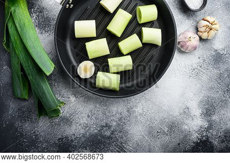 Raw Braised Leeks On Grill Pan Uncooked With Herbs Ingredients , On Textured Grey Background Top Vie