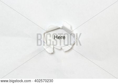 Word Here On White Isolated Background, The Inscription Through The Wound Hole In Paper. Concept Of