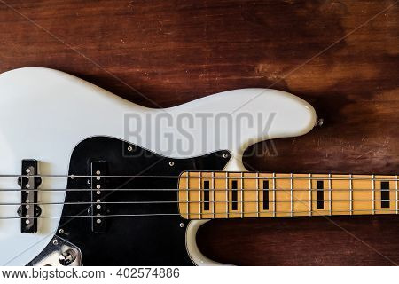 White Electric Bass Guitar On Wood Background With Copy Space