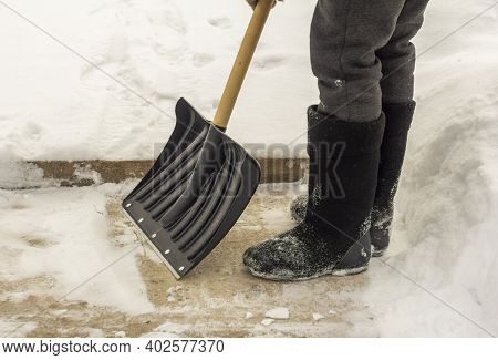 A Man In Felt Boots, With A Shovel In His Hands, Removes Snow From The Sidewalk After A Snowfall.
