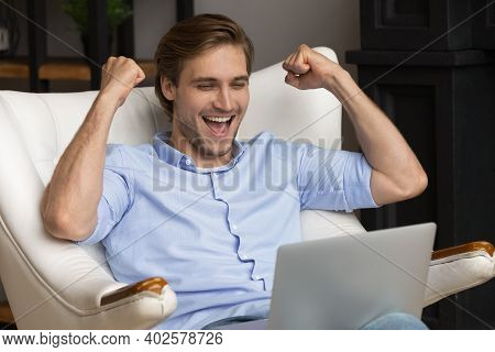 Excited Man Triumph Winning Lottery On Laptop