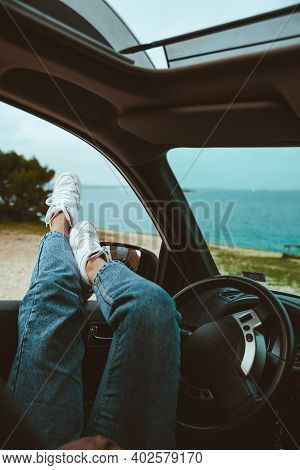 Woman Resting In Car Parked At Sea Beach