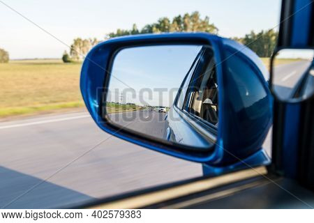 Rear View In The Side Mirror Of A Blue Sedan With The Reflection Of A Cars On An Asphalt Road On A S