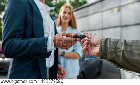 Selective Focus On Dealer Giving Car Keys To Buyer In Suit With Young Woman On Background, Widescree
