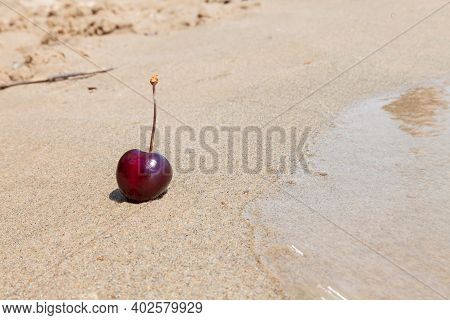 One Berry Of Ripe Red Cherries On The Beach By The Sea On The Sand, A Romantic Seductive Dessert On