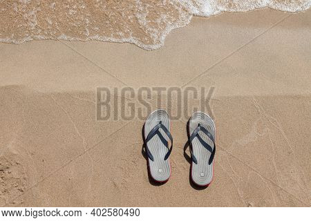 A Pair Of Sandals With Red Soles On A Sunny Beach With Sand Near The Seashore On A Summer Day. Rest