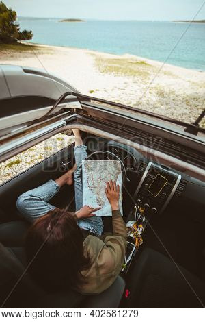Woman Sitting In Car Checking Map Sea Beach On Background