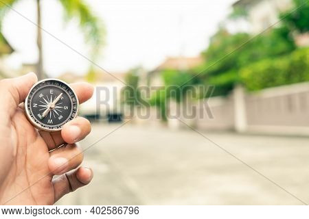 Man Hand Holding Compass On City And Car Blurred Background Using Wallpaper Or Background Travel Or