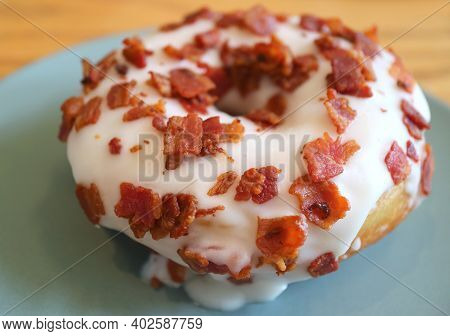 Closeup Of Mouthwatering Maple-glazed Bacon Doughnut On A Plate
