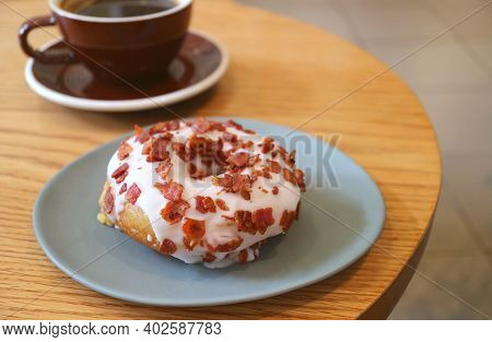 Plate Of Delectable Maple-glazed Bacon Doughnut With Blurry Hot Drink On The Backdrop