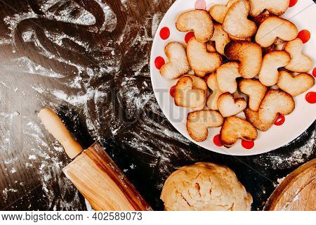 Cookies In Shape Of Heart For The Saint Valentine's Day. Dough, Flour, Baking Pan, Round Wooden Cutt