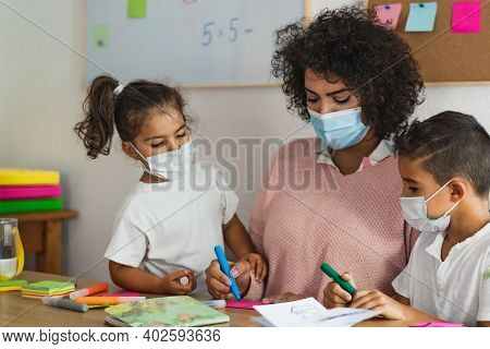 Teacher With Children Wearing Face Mask In Preschool Classroom During Corona Virus Pandemic - Health