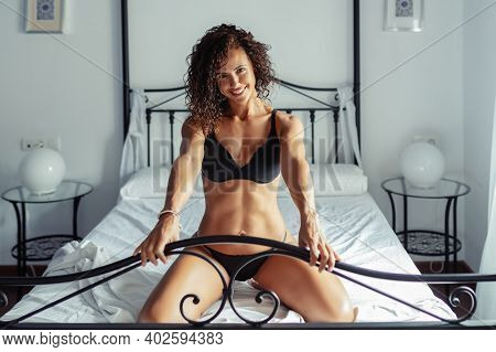 Middle-aged Woman In Lingerie Posing On The Bed