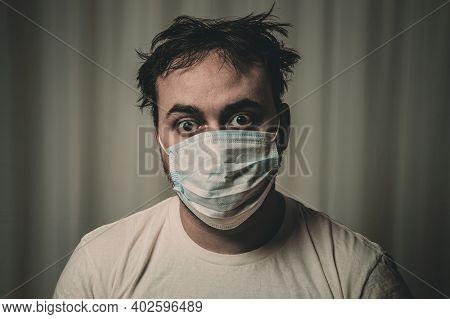 Unshaven Man In A Medical Mask With Tousled Hair Looking At The Camera. On White Background. Image T