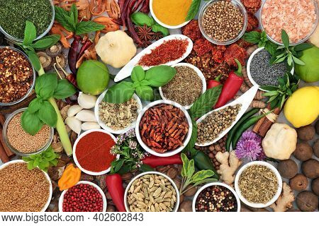 Large herb and spice seasoning collection for culinary classics with herbs and spices in porcelain bowls and loose. Abstract healthy herbs background. Flat lay, top view.