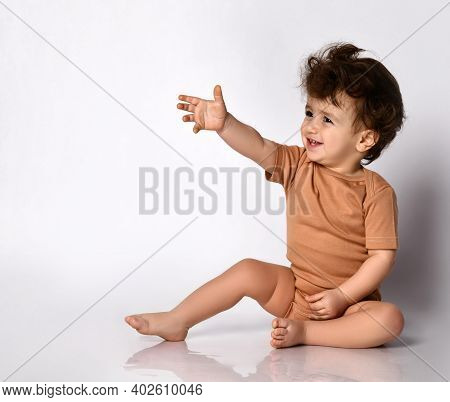 Cute Little Curly Boy Dressed In A Brown Bodysuit Extends His Hand Forward Sitting Barefoot On A Gra