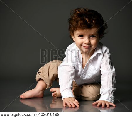 Cute Stylish Handsome Barefoot Baby Boy In Trendy Outfit Smiling Slyly, Grinning Looking At Camera.