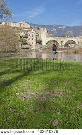 Besalu, Spain - Dec 28th, 2019: Fluvia Riverside With Medieval Bridge At Bottom, Besalu. Garrotxa, G